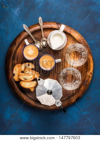 Coffee espresso in cups with italian cantucci, cookies and milk in jug on wooden serving round board over dark blue painted plywood background, top view, vertical composition