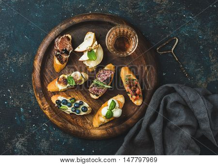 Italian crostini with various toppings and glass of wine on round wooden serving tray over black plywood background, top view