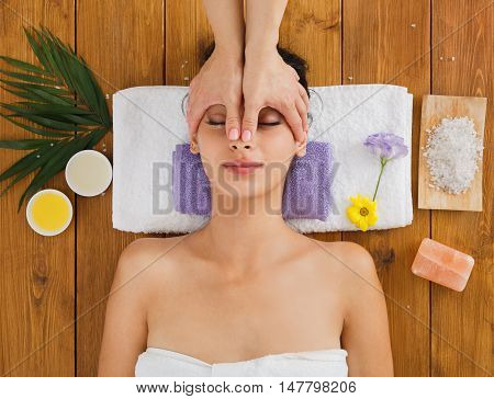Massagist with woman patient in aroma spa wellness center. Professional face lifting and body massage to beautiful girl in cosmetology cabinet or beauty parlor.