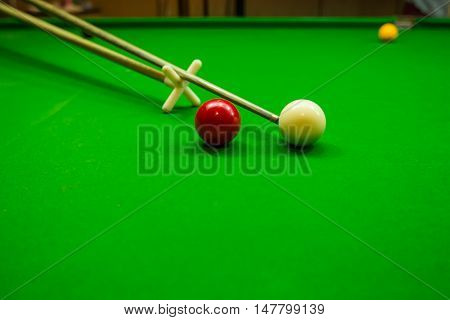 Snooker cue with snooker ball on green table background
