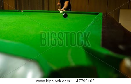 Men's hand hold Snooker cue with snooker ball on green table background