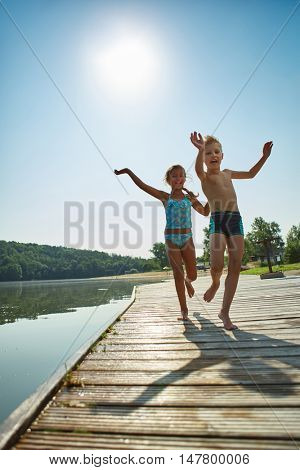 Two kids playing on a pier at the lake and having fun