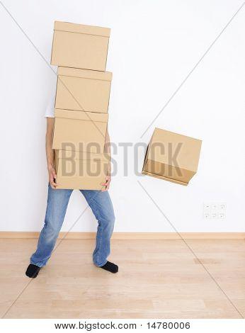 Junger Mann tragen und Ablegen von seinem Stapel von Umzugskartons