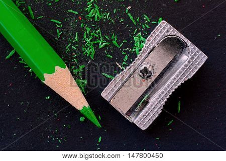 green wooden pencil pencil shavings and sharpener