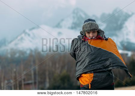 Woman covered with sleeping bag in front of a snow covered mountain