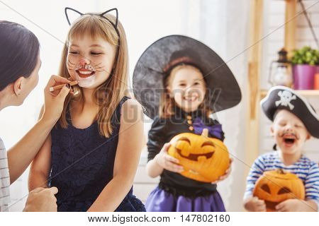 Happy family prepares for Halloween! Young mom and her kids in carnival costumes celebrate the holidays.