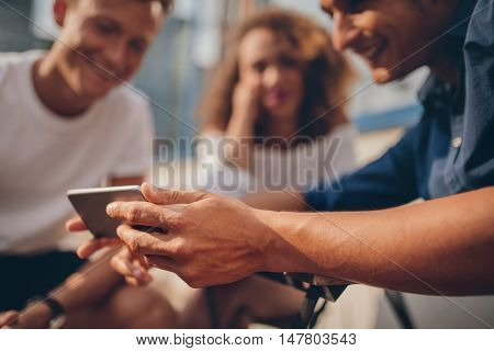 Young friends sitting outdoors and looking at smartphone. Group of people watching video on the smartphone. Focus on mobile phone in hand.