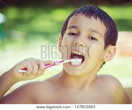 Happy children on summer garden having fun and happy time brushing teeth after outdoor bath