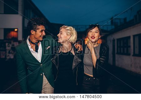 Diverse group of friends walking on the street at night. Multiracial young man and women enjoying outdoors in evening.
