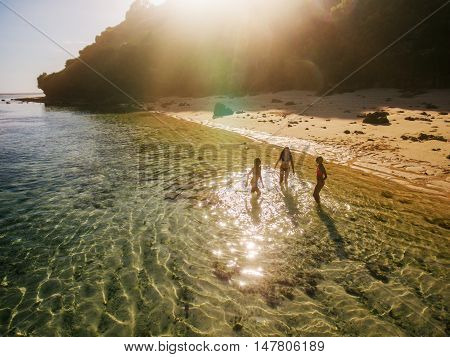 Aerial view of three young female friends standing in sea water. Women enjoying vacation on tropical beach.