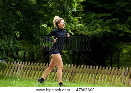 Healthy Young Woman Running In Park