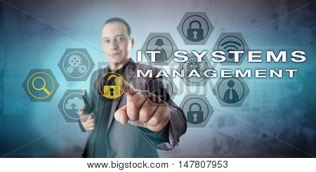 Experienced network administrator is activating IT SYSTEMS MANAGEMENT onscreen. Kind yet tense and concentrated facial expression. Information technology concept for computer systems administration.