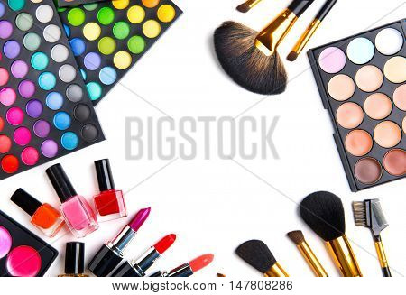 Makeup. Make-up Set Palette with colorful eyeshadows. Various cosmetics Brushes, lipgloss, lipstick, rouge, eyeshadow tints, foundation isolated on a white background. Make up artist tools