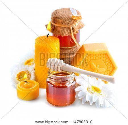 Honey, natural wax and wax candles isolated on white background. Spa and alternative medicine concept
