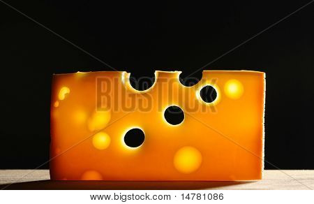 Swiss cheese over black background