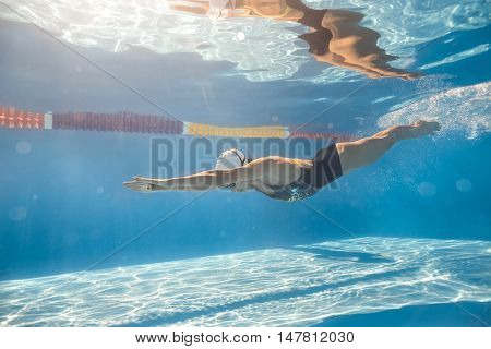 Great swimmer swims in crawl style underwater in the swim pool outdoors. She wears black-gray swimsuit, white swim cap and swim glasses. Sunlight falls from above. Her body reflected in water surface.