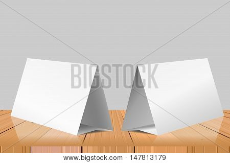 Blank Table Tent isolated on wooden table background. Paper horizontal triangle cards on white background with reflections. Front. left and right view. Vector illustration.