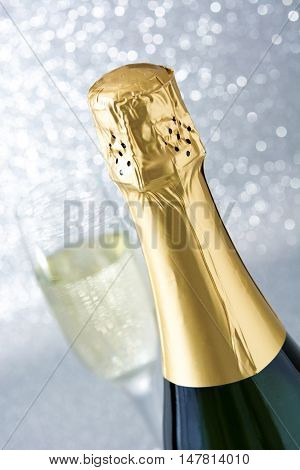 Champagne bottle with glass cup on brilliant silver background