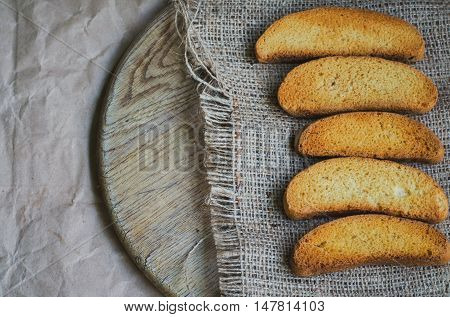Rusk white bread on background of canvas background and wrapping vintage paper toned and faded