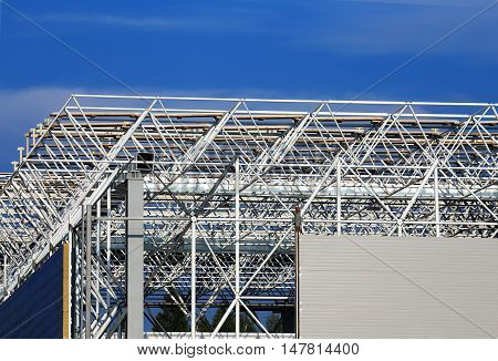 Construction site. Installation of coverings on a skeleton of industrial building during construction