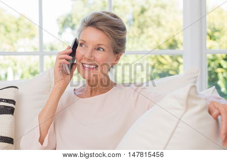 Senior woman talking on her mobile phone. Senior woman has a happy conversation at cellphone. Smiling senior woman using phone sitting on couch at home. poster