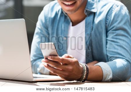 Close up of a student man using smart phone and laptop in cafe. Closeup of hand of a young man using smartphone. Happy african man reading a message phone outdoor.