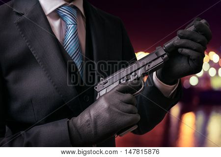Murderer Or Killer Holds Pistol With Silencer In Hands At Night.