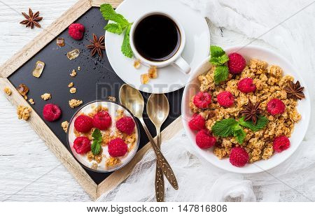 Breakfast, food, still life concept. Coffee muesli granola berries homemade yogurt on a rustic white wooden table. Selective focus top view flat lay overhead
