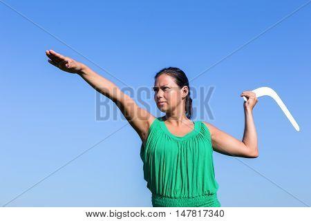european woman throwing white boomerang in blue sky