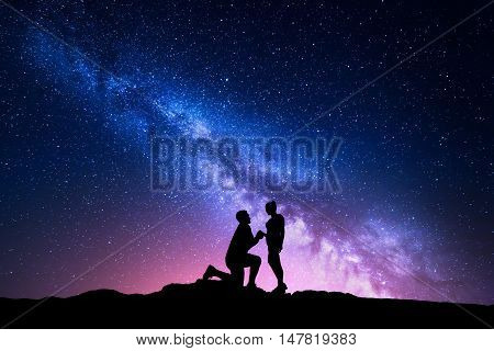 Milky Way. Night landscape with silhouettes of a man making marriage proposal to his girlfriend and starry sky. Silhouette of lovers. Couple relationship. Milky way with people. Universe