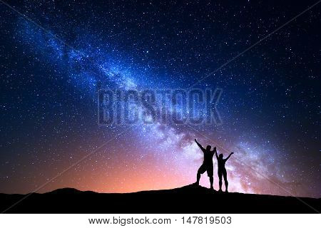 Milky Way. Colorful night sky with stars and silhouette of standing happy man and woman with raised up arms on the hill. Blue milky way with people on the mountain. Background with beautiful universe