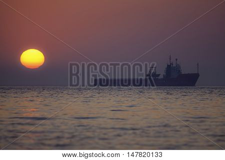 A ship sails perfectly across the horizon on a morning when a low bank of mist filters the sun's rays into a beautiful red pink glow.