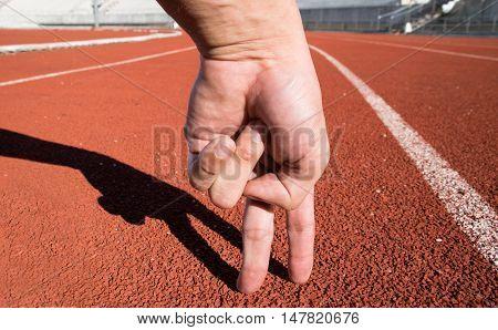 Two Fingers Man Running On Running Track At Sport Stadium