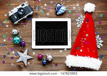 Christmas and New year background with tablet Santa's hat old fashioned camera and decorations. Place for text. Mock up flat lay top view.