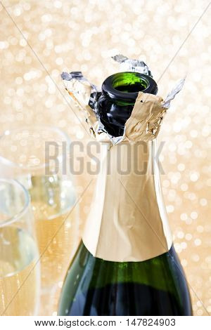 Champagne open bottle with glass cups on brilliant golden background