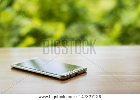 Gold smartphone on wooden table with blurry green tree background selective focus. Put down your smart phone concept