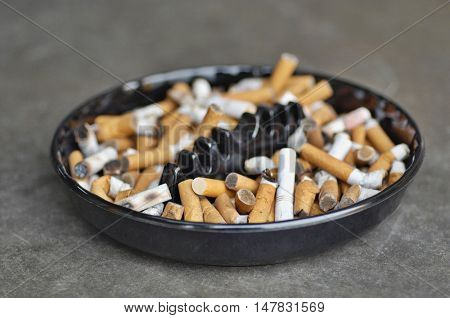 Full ashtray of cigarettes on table, close-up