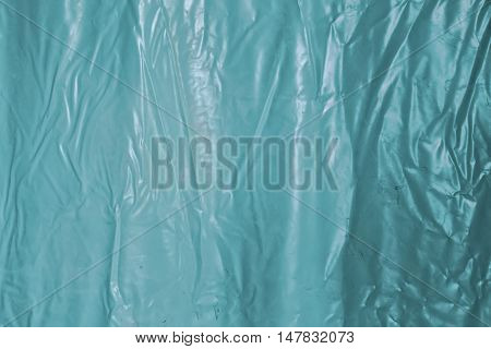 Texture of blue waterproof crumpled oilcloth or cellophane