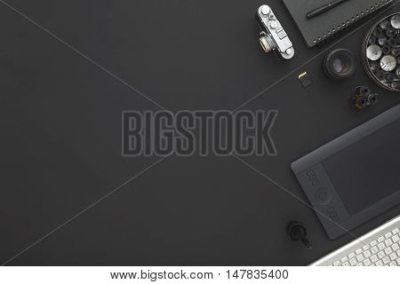 Work space on black table of a creative designer or photographer with laptop tablet camera and other objects of inspiration and copy space. Stylish home studio concept of technology trends.