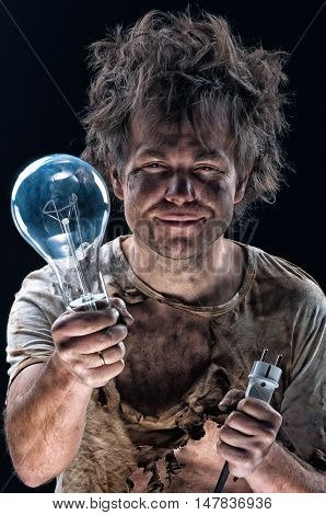 Portrait of burnt man with light bulb and electric plug over black background. Young man with dirty burnt face in funny sad expression in electricity DIY has a electric shock.