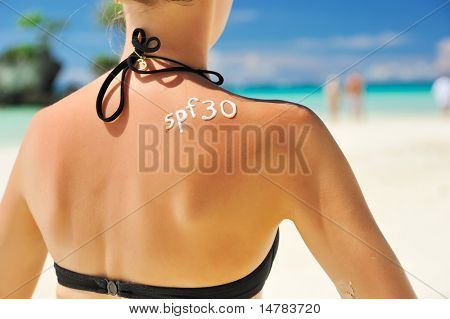 Sunscreen lotion over tan woman skin made as SPF 30 word