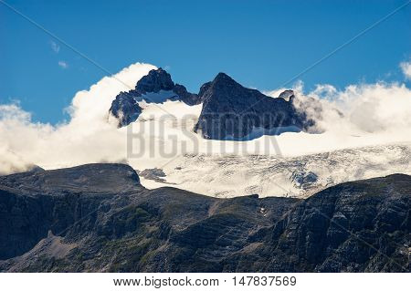 Peaks of Dachstein massif covered by glacier and clouds Austria