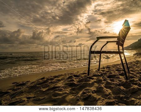 Silhouette of wooden armchair against the rising sun at the beach