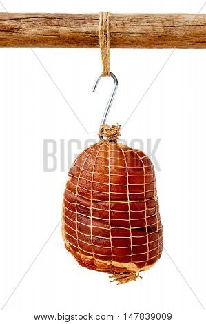 Smoked boneless pork ham hock wrapped in netting hanging on a hook from a wooden pole isolated on white