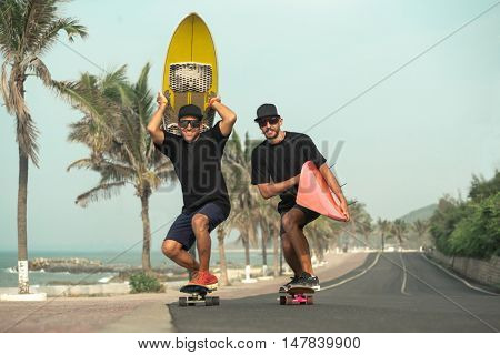 Surfers having fun with surfboards on the road