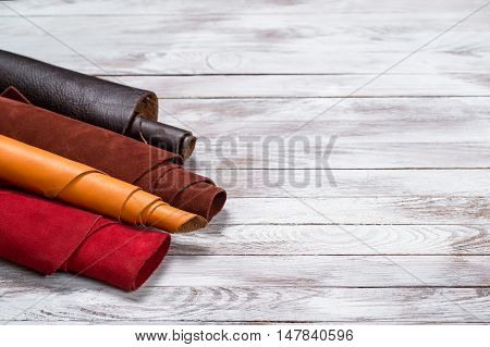 Brightly colored leather in rolls on the white wooden background. Leather craft. Copy space.