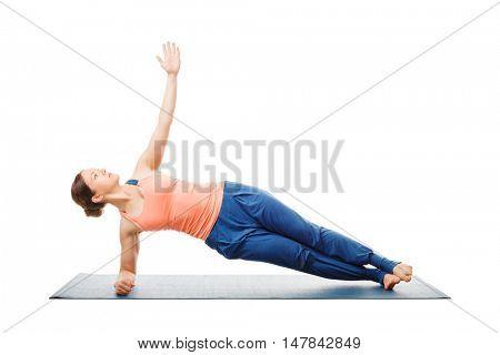 Hatha yoga - sporty fit woman doing yoga asana Vasisthasana - side plank pose modification for wrists isolated on white background