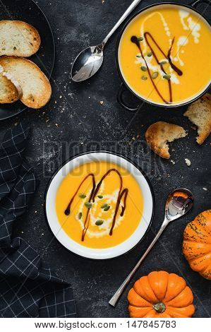 Pumpkin cream soup in bowl garnished with heavy cream, pumpkin seeds and balsamic vinegar. Side view. Toned image. Comfort food, fall / autumn concept.