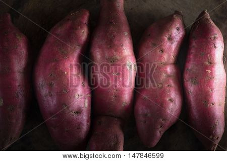 Raw sweet potatoes on wooden background. Sweet potatoes on dark tone.