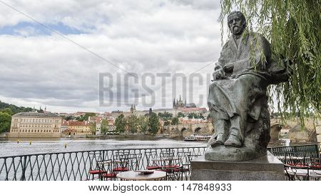 PRAGUE,CZECH REPUBLIC,JULY 6, 2016: Statue of Bedrich Smetana infront of The Bedrich Smetana Museum, Charles Bridge and St. Vitus Cathedral with Prague Castle district can be seen on background.